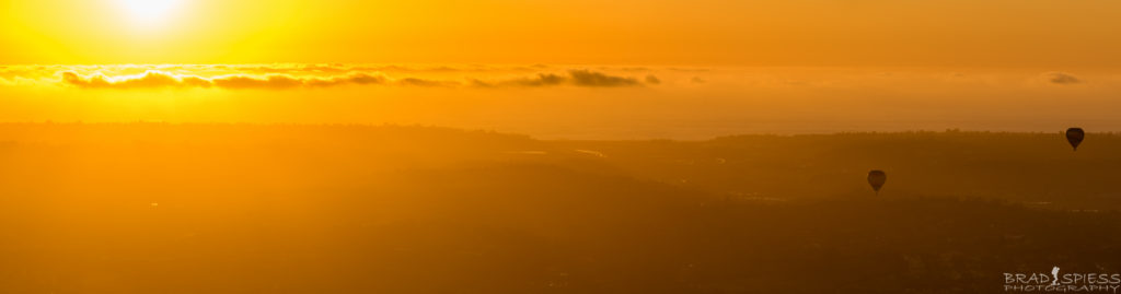 Looking west at the setting sun and balloons in Rancho Santa Fe from the top of Blacks Mountain.
